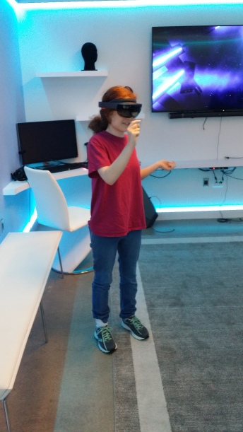 A student in a red shirt with blue denim standing in a room with a large screen TV and desk top computer while she uses the VR headset.