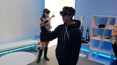 A student in a dark blue hoodies with white strings and another student behind him in a grey shirt with black knee boots stand in a room with a long bench, circle rug, large bookcase, with blue lighting behind it while they use the VR headset.